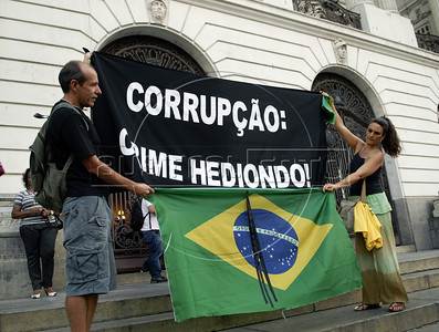 "A couple hold a banner and a brazilian flag during a protest against corruption, following recent scandals which include the dismissal of four ministers,in Rio downtown, Rio de Janeiro, Brazil, september 20, 2011. In the banner says:""Corruption: heinous crime"".(Austral Foto/Renzo Gostoli)"