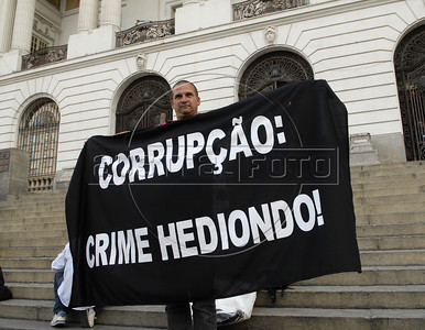 "A man holds a banner during a protest against corruption, following recent scandals which include the dismissal of four ministers,in Rio downtown, Rio de Janeiro, Brazil, september 20, 2011. In the banner says: ""Corruption:heinous crime"". (Austral Foto/Renzo Gostoli)"