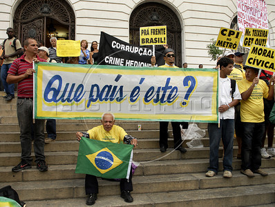 "People hold banners during a protest against corruption, following recent scandals which include the dismissal of four ministers,in Rio downtown, Rio de Janeiro, Brazil, september 20, 2011. In the big banner says: ""What country is this?"". (Austral Foto/Renzo Gostoli)"