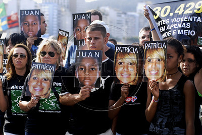 Pictures of Juan Moraes, who died after running into police gunfire in a street shooting, and others victims of violence are showing by parents and friends during a protest against impunity on Copacabana beach, Rio de Janeiro, Brazil, July 31, 2011. Rio de Janeiro, that will host the 2016 Olympic Games, has one of the deadliest police forces on the world and in the last five years they kills more of 30.000 peoples. (Austral Foto/Renzo Gostoli)