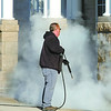 John Reed of Pioneer Restoration waits for vapor to dissipate after power-washing graffiti from columns at the Lebanon Public Library Thursday.