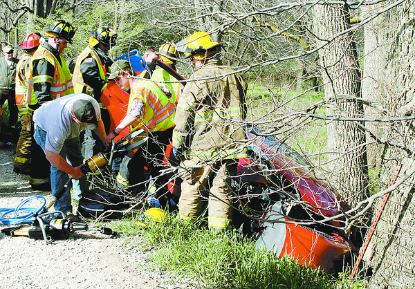 Firefighters from three departments work to remove a Frankfort woman from her car Monday afternoon on Lost Road near the Boone-Clinton county line.