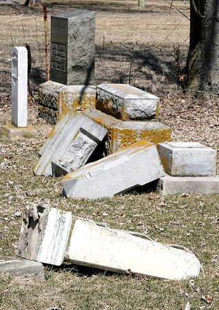 Reporter photo by Rod Rose<br /> Broken tombstones lie in a row at the Old Cemetery in Thorntown, where about 100 grave markers were vandalized by two children last week.