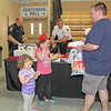 Rod Rose The Lebanon Reporter<br /> HOME SHOW FANS: Kevin Diniger, Lebanon, smiles as his daughters Hattie, 3, and Della, 6, visit the public safety booth at the Home Show Thursday afternoon. Lebanon Police Deputy Chief Brad Bailey and Deputy Fire Chief Mike Baird were distributing items to visitors.