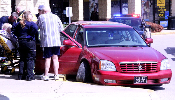 """FORTUNATE OUTCOME: Judith Mullen, 76, of Darlington, is loaded onto a stretcher after her 1995 Cadillac DTS caromed down N. Lebanon Street before coming to a stop in front of Goody's. The vehicle mounted the sidewalk before striking the curb. Lebanon Police officer T.J. Nelson said the passenger, Donald Mullen, turned the ignition key off headinng south on SR 39 after he saw a """"blank look"""" come across Judith's face. Donald then grabbed the wheel from th epassenger seat and steered the car down N. Lebanon St. before crashing into the curb and snapping the drive shaft of the right front wheel. Nelson said the incident could've been much worse had one of the pedestrians on the sidewalk been struck."""
