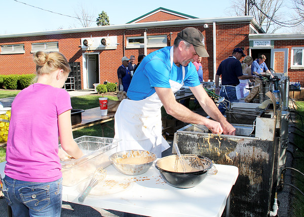 Rod Rose The Lebanon Reporter<br /> BATTERING UP: Joe Leising, aided by his daughter, Sydney, 13, preps fish for the fryer at the St. Joseph Knights of Columbus fish fry Friday at the Boone County 4-H Fairgrounds. The event is the second of three community dinners held during the Home and Garden Show.