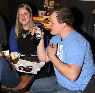 SHARING MEMORIES: Tyler Bennett (right) and girlfriend Blair Martin, 24, talks with friends and family during a The Price is Right viewing party at Lebanon's Buffalo Wild Wings