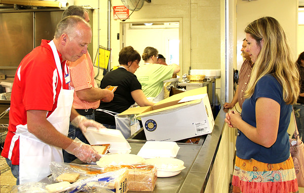 TO GO: Dan Brownlee, Boone County resident, wraps up one of three carry out dinners for Sarah Glass, Sheridan, at Saturday's 4-H Pork Chop and Chicken Dinner. Held the final day of the Boone County Home Show, guests had the option of pork chops or chicken, applesauce, baked beans, green beans and chips. The Extension Homemakers sold apple, cherry, pineapple coconut, and pumpkin pies, along with oatmeal cinammon bars. Busy throughout the evening, there were two service lines with an additional carry-out line available. The Clinton Country Kids were first in the BBQ Sales contest with Perry Future Farmers and the Clinton Clintoneers coming in second and third, respectively. The 4-H Junior Leaders helped with drink service and clearing tables throughout the event.