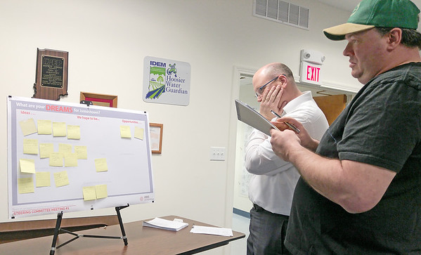 COMPREHENSIVE PLANNING: HWC Engineering director of planning Corey Whitesell (left) looks at Post-It notes created by Jamestown residents describing their hopes for Jamestown's future.