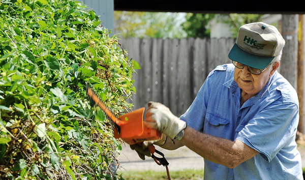 """Trimming the Verge<br /> Globe/T. Rob Brown<br /> Elmer Geller, of Neosho and formerly of Joplin, takes advantage of the warm weather to trim the verge Tuesday morning, April 3, 2012, on Pennsylvania Avenue, near 20th Street. Geller said honeysuckle had overrun the fence and was doing damage. """"My wife wanted it done, so I'm getting it done,"""" he said."""