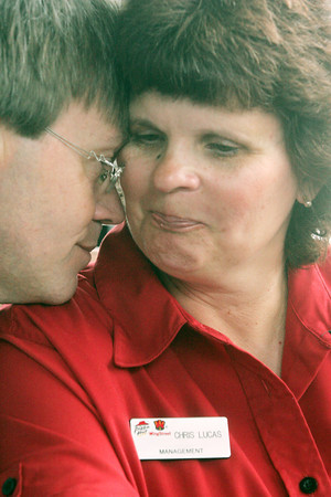 Globe/Roger Nomer<br /> Michael Praytor comforts his wife Pamela J. Praytor as she talks about her son Chris Lucas, who died at the Range Line Pizza Hut in the May 22 tornado.  Praytor wore her son's nametag to honor him while working at the grand reopening of the restaurant on Friday.