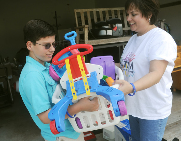 Globe/Roger Nomer<br /> Nico Bowman takes a basket from his mother Tania as they prepare for this weekend's rummage sale.
