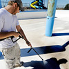 Globe/T. Rob Brown<br /> Matthew Yakel, co-owner of Yakel Painter, of El Dorado Springs, Mo., sprays down the surface of the Cunningham Park Pool Tuesday morning, April 24, 2012, in preparation for a new paint job. The pool's new four-flume slide can be seen in the background. The pool was damaged by the May 22, 2011, tornado.