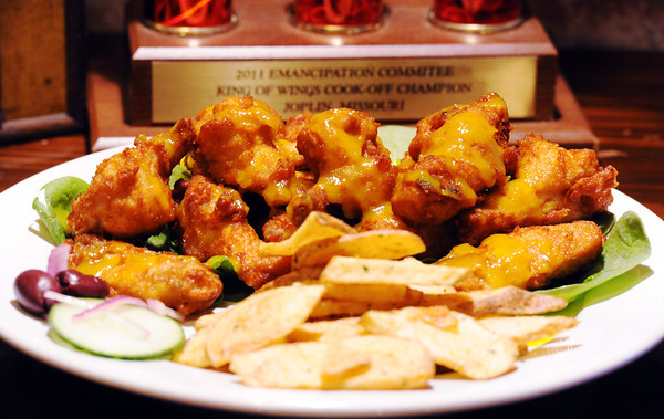 Globe/T. Rob Brown<br /> Mango wings at Caldone's, 218 S. Main St., Joplin, in front of the base of the 2011 Emancipation Committe King of Wings Cook-Off Champion trophy.