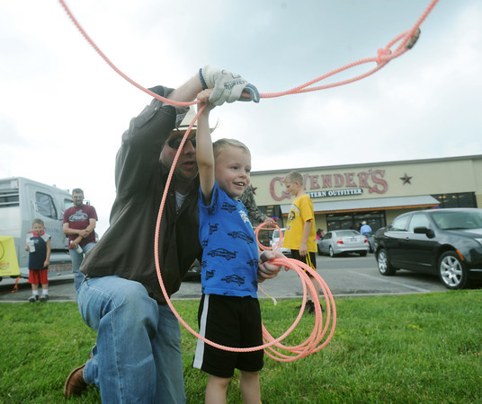 Globe/Roger Nomer<br /> Will Cooper shows Drayton Tune, 3, the ropes during a lasso demonstration by Cactus Ropes at the grand opening of the Cavender's Western Outfitter store on Range Line Road on Saturday afternoon.