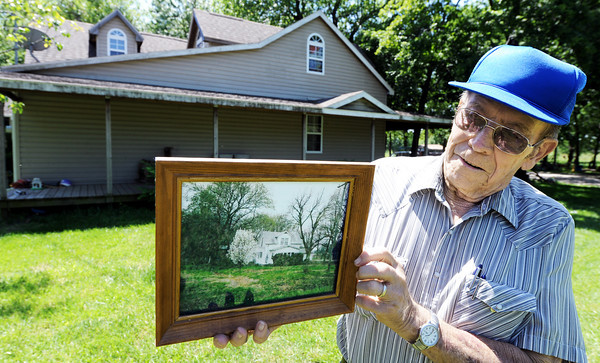 Globe/T. Rob Brown<br /> Bill Scott holds a photo of what the Scott family home looked like from 1935 to 2001 in front of the property near Parsons, Kan., Wednesday afternoon, April 25, 2012. In 2001, the property was remodeled and 1,600 square feet were added. Six generations have lived on the property.