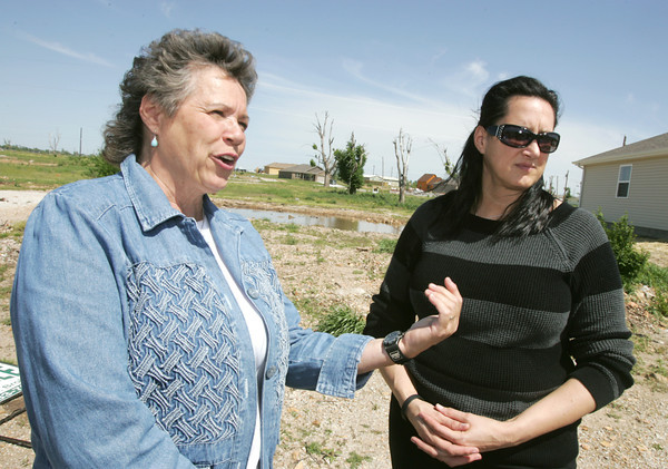Globe/Roger Nomer<br /> Jan Finney, left, and Teresa Newton talk about Newton's troubles with her insurance company during an interview at the site of Newton's former house along Wisconsin Street.