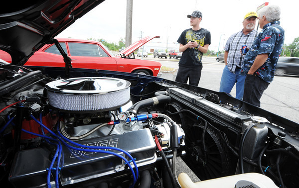 Globe/T. Rob Brown<br /> Attendees (from left) Patrick Phillips, of Joplin, Pete Kozak, of Webb City, and Roger Pendergraft, of Joplin, talk shop next to the engine of Kozak's 1979 El Camino and Phillips' father's 1971 Nova (background) during the TitleMax Route 66 Car Show Saturday morning, April 14, 2012, just off of West 7th Street in Joplin.