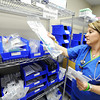 Globe/T. Rob Brown<br /> Christina Leggett, senior staff R.N., gathers up supplies to assista a patient as she wears a necklace which bears the thumbprints of Teresa and Taylor Kemp, a cross that holds a lock of her sister's hair and features angel wings, Monday morning, April 16, 2012, at the new Mercy temporary hospital.