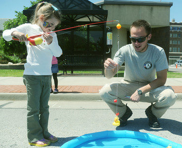 Globe/Roger Nomer Dane Sosniecki, with Americorp NCCC from Moberly, helps Samantha Goade, 5, with her duck catch during Saturday's April Showers Art and Craft Fair presented by Way Beyond Events in downtown Joplin.