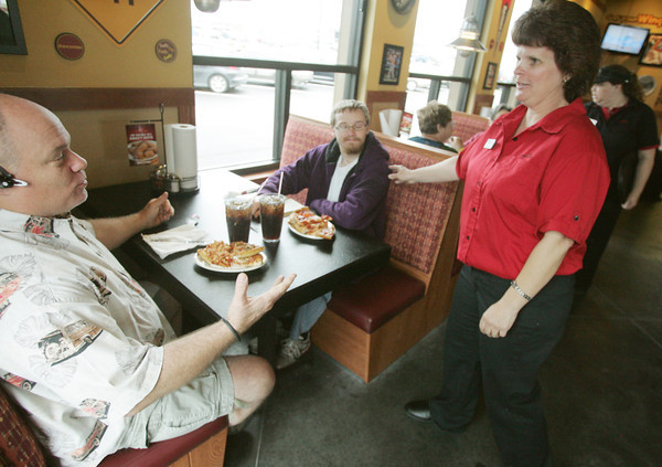 Globe/Roger Nomer<br /> Pamela J. Praytor talks with Richard, left, and Michael Arnold-Yeager during the reopening of the Range Line Pizza Hut on Friday.