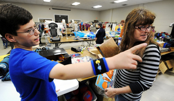 Globe/T. Rob Brown<br /> Niko Bowman, 11, of Joplin, who has autism, points to some items he believes Tammy Gibson, of Riverton, Kan., might be interested in during the Fourth Annual Niko's Sale for Autism Saturday morning, April 14, 2012, at the Joplin Museum Complex.