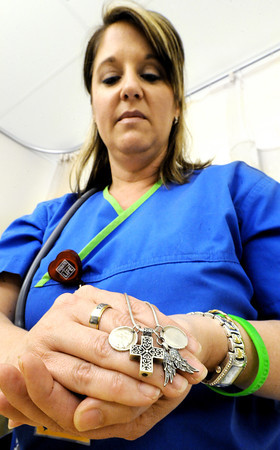 "Globe/T. Rob Brown<br /> Christina Leggett, senior staff R.N., holds a necklace she frequently wears, which bears the thumbprints of Teresa and Taylor Kemp, a cross that holds a lock of her sister's hair and features angel wings, Monday morning, April 16, 2012, at the new Mercy temporary hospital. The ring reads ""TKx2 -- Miss You."" The green bracelet reads ""Donate Life."""