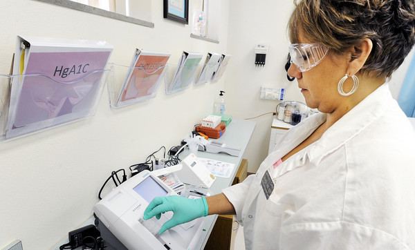 Globe/T. Rob Brown<br /> Community Clinic volunteer coordinator Carthena Green, RMA (Registered Medical Assistant), uses the clinic's new laboratory to run an HgA1C test on a patient's blood sample Monday morning, April 23, 2012.