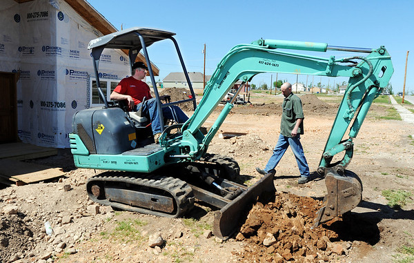 Globe/T. Rob Brown<br /> Larry Jump walks past a mini excavator operated by volunteer Ben Muilenburg, of Inwood (Iowa) Christian Reformed Church Friday afternoon, April 6, 2012, at her Joplin home. The church group was volunteering through Catholic Charities, which has been helping the Jumps finish their home, to dig the family's water line.
