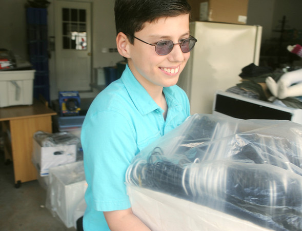 Globe/Roger Nomer<br /> Nico Bowman carries a box as he helps load a truck for a rummage sale this weekend to benefit the Ozark Center for Autism.