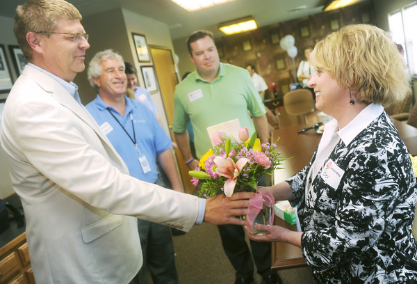 Globe/Roger Nomer<br /> (from left) Brian Berkstresser, board president, Bill Aquino, treasurer, and Andy Perigo, incoming president, welcome new United Way Director Bev Crespino-Graham with flowers on Thursday afternoon.