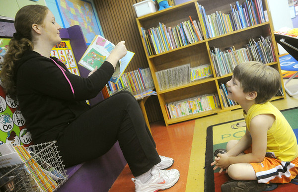 Globe/Roger Nomer<br /> Cale Handshy, 5, listens to a story from Kelli Zellner at the Pittsburg YMCA daycare on Tuesday.