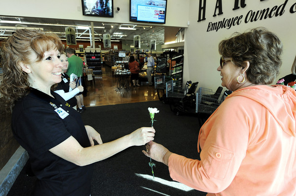 Globe/T. Rob Brown<br /> Valerie Schweda, left, general merchandise with Harps, hands a flower to customer Linda Fullerton, of Joplin, Wednesday morning, April 18, 2012, during the Airport Drive store's grand opening.