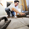Globe/T. Rob Brown<br /> Amy Jump scrubs the excess grout from a new bathroom tile Friday afternoon, April 6, 2012, at her Joplin home. Catholic Charities has been helping the Jumps finish their home.