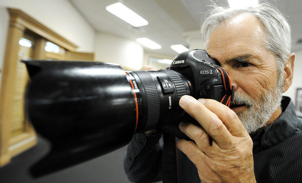 Globe/T. Rob Brown<br /> J.B. Forbes, chief photographer for the St. Louis Post-Dispatch, takes photos of people looking over a series of 19 photo enlargements, size 20-by-30, shot by him and his staff, donated to the city of Joplin Friday afternoon, April 27, 2012, at Joplin City Hall. A group of 44 images were part of the Journalists for Joplin effort where photos were sold through silent auction to raise funds for Joplin Tornado First Response Fund. Of those 44 images, 19 were donated back by the auction winners to be given to the city of Joplin.