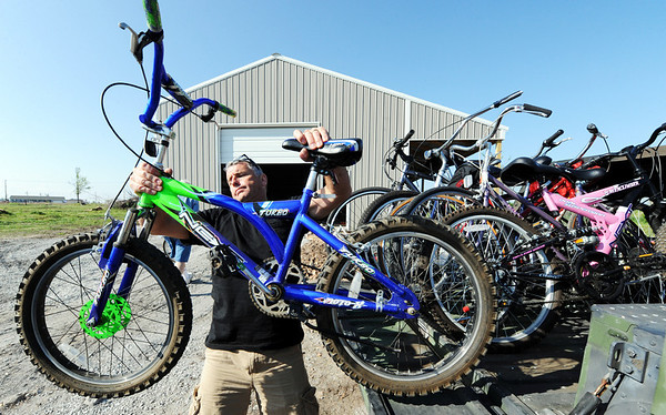 Globe/T. Rob Brown<br /> Kiwanis Club of Ozark Coast member Trevor Downey, of Osage Beach, lifts one of about 20 bicycles donated to the Joplin Kiwanis Club for children affected by the tornado during a delivery Monday morning, April 2, 2012, in Joplin. Downey, who is also the police chief at Lake of the Ozarks, is a bicyclist and a co-organizer for the second-chance bicycles project. In addition to the bicycles, the group donated helmets and other items, such as tricycles, scooters, wagons and a skateboard.