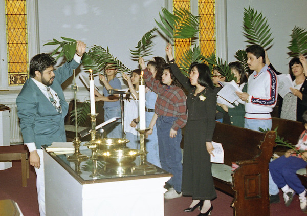 THE GOSHEN NEWS | APRIL 1, 1996 <br /> The Rev. Oscar Ramos, far left, leads the congregation of La Sagrada Familia in celebration using palms Sunday at First United Methodist Church, 214 S. Fifth St. Several local churches observed Palm Sunday during their services, and special Easter services are also being planned.