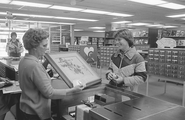 """THE GOSHEN NEWS   APRIL 16, 1980<br /> It was National Library Week and the Goshen Public Library celebrated with a week of activities. Pictured, Karen Moore Beltler, 1321 S. Eighth St. at right, checks out a painting by artist Jerzy Titled """"Fuchsia"""" The Library offered about 200 framed reproductions for check-out. Paintings were checked out six weeks at a time."""