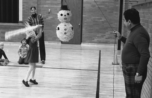 THE GOSHEN NEWS | November 5, 1976<br /> Lisa Garcia, daughter of Mr. and Mrs. Israel Garcia, celebrated her sixth birthday with her kindergarten class as they tried to break a pinata in the gym of Parkside School Thursday afternoon. Lisa's grandmother, Sarah Garcia, and Lisa's father, at right, made the pinata and supervised the birthday party for Mrs. Jan Yordy's afternoon class. Mrs. Yordy is standing in the background.