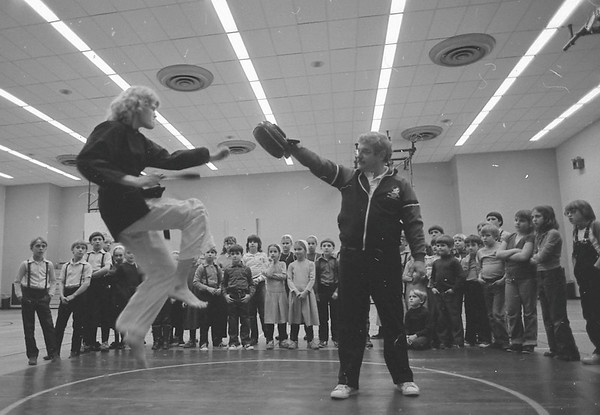 Debbie Edwards, 20, shown kicking in the air, and Phil Redd, 24, presented a martial arts show Wednesday for students at Topeka Elementary School. Edwards, originally from Rome City, is presently ranked fourth best martial artist in the world, and she is a member of the United States Olympic team. Redd, a black belt, has studied 12 different syles of martial arts. A former national champion, he is from Terre Haute. Together they run three martial arts schools in northeast Indiana located at Kendallville, Cromwell and Prarie Heights Middle School. Goshen News photo published Feb. 8, 1984