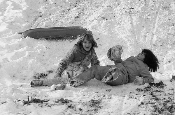 THE GOSHEN NEWS | JAN. 26, 1980<br /> Kelly Espinoza and Kathy Paluchniak share a new plastic sled on a hill along Dewey Avenue near Berkey Avenue Friday afternoon. The two were among a crowd of young people who used the snow on the hill after school Friday. More sledding and skiiing maybe on tap for area residents this weekend as sub-freezing tempertures are predicted the next two days.