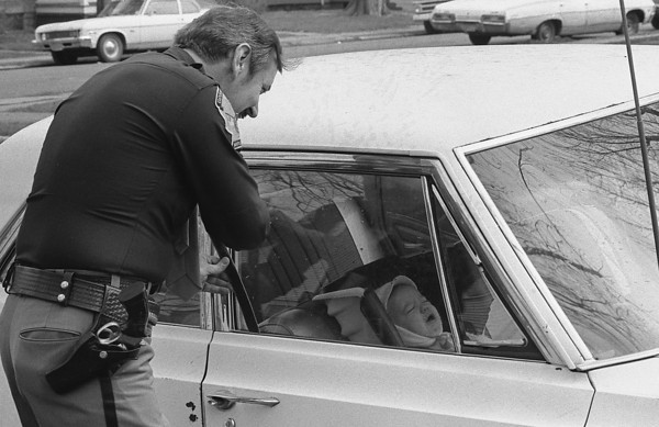 "THE GOSHEN NEWS PHOTO  April 27, 1979<br /> Kurt Unrue, 8 months of age, voices his displeasure the best way he knows how about being locked in the family car as Goshen Police Ptl. Sam Johnson works to open the door with a slim-jim device. Goshen police get a variety of these calls from motorists who accidently lock the keys in their car. This ""emergency"" occurred recently in front of the home of Mr. and Mrs. David Unrue, 307 S. Seventh St., when Mrs. Unrue locked the keys in the car while her husband was away from home on reserve policeman duties. Although Ptl. Johnson wasn't able to open the door on his first try, an unidentified neighbor managed to open the door with a coat hanger and ""rescue"" little Kurt."