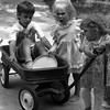 THE GOSHEN NEWS PHOTO  BACK WHEN Aug. 3, 1993<br /> Stephanie Chupp, 2 1/2, tries pulling 5-year-old Ben Horst in a Radio Flyer wagon along Berkey Avenue Monday afternoon. Looking on is Ben's sister, 2-year-old Rosie.