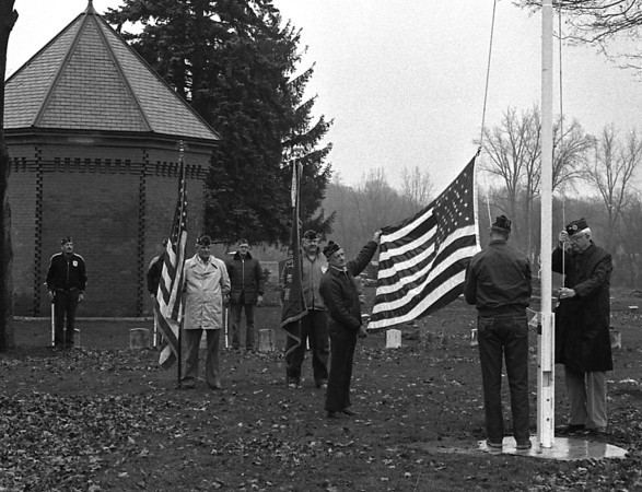 THE GOSHEN NEWS PHOTO  BACK WHEN Nov. 10, 1985<br /> Members of the three Goshen veterans service organizations met Saturday afternoon for a brief dedication ceremony of a new flagpole in the veterans section at Oak Ridge Cemetery. The steady Saturday rainfall stopped just long enough for the ceremony, which included a four-gun salute by the honor guard. Pictured above in the foreground are James Hughes, commander of the Disabled American Veterans, holding the American flag with B.G. Hoogenboom, commander of the Veterans of Foreign Wars, while Jim Morse, American Legion commander, prepares to raise the flag. Color bearers are Ted Smith and Jack Pangburn, while those in the background include Max Snyder, Chuck Kyle, Bill Rieth, Jim Drummond and Al Richmond. American Legion Post 30 and the Goshen DAV hosted traditional Veterans Day services at 11 a.m. today.