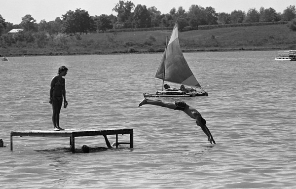 THE GOSHEN NEWS PHOTO  BACK WHEN JULY 13, 1983<br /> As the thermometers hold around 90 degrees this week, one of the best places to find relief is at a nerarby lake or pool. Swimming, diving and sailing are sports these people enjoyed Tuesday at Shipshewana Lake, just northeast of that LaGrange County town. While the young people cool off at the platform near the public beach on the east side of the lake, the sailor cruises across the lake in the background. Because News Photographer Tom Roberts used a long telephoto lens when he took this photo, the lake is compressed and the west shore appears much closer than it really is to the east shore. Thermometers hit 91 degrees at Goshen Monday, and it was 88 on Tuesday afternoon.