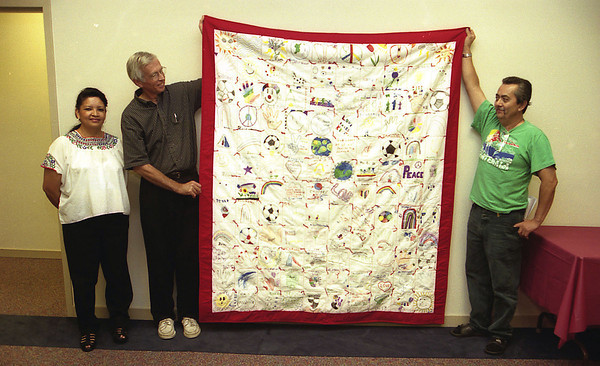 THE GOSHEN NEWS PHOTO  BACK WHEN June 29, 2000<br /> At a Goshen Human Relations Commission meeting Wednesday, Magaly Quan, Art Smoker and Otto Quan display a quilt recently completed by North Goshen Mennonite's women's sewing group. At the HRC Diversity Day in 1998, children were invited to make drawings on quilt blocks. Ruby Nussbaum of North Goshen Mennonite then stitched the quilt together and the sewing group recently completed the quilt.