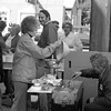 THE GOSHEN NEWS PHOTO  Back When Sept. 28, 1980<br /> Donna Kuhn pours batter into a device used to make apple fritters, while Lavon Kuhn is busy turning the fritters. The Kuhns, of Nappanee, were making fritters as a part of the exhibits Friday and today during the Nappanee Apple Festival. Other booths and exhibits included antique cars, arts and crafts, apple butter making, rides and wood carving and live entertainment was also featured. There was also a Volk Run, water ball contest and softball tourney.