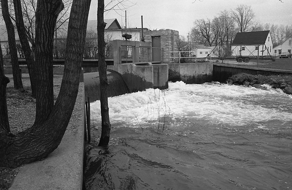 THE GOSHEN NEWS PHOTO  Back When April 11, 1985<br /> Water flowing over the Syracuse dam filled Turkey Creek to capacity recently after heavy spring rains in Kosciusko County swelled both Lake Wawasee and Syracuse Lake. One of two gates at the dam is open and there is 13 inches of water flowing over the spillway. The water level was at 9.84 feet Wednesday at the dam, more than one foot above the spillway.