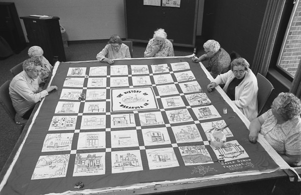 THE GOSHEN NEWS PHOTO  Back When February 9, 1980<br /> Members of the Wakarusa Historical Society are making a quilt with pictures of the town's history sewn into the squares of the donated material. The project is planned to raise funds for the town's museums. Mary Ann Troxel sketched all 38 small blocks and the large one in the middle and ladies of the community embroidered the blocks, finishing last month. Everyone is welcome to help stitch the quilt in the library meeting room through Feb. 16. The work will be displayed at the library until it is sold through bids March 29. Pictured above, clockwise from left, are Minerva Overholt, Inez Eby, Frankie Myers, Marie Chupp, Hazel Dils, Jay Freed and Grace Flory.