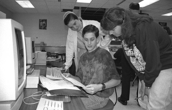 "THE GOSHEN NEWS PHOTO  BACK WHEN Nov. 3, 1995<br /> An unusual combination of ""students"" look over some schoolwork at NorthWood High SchooL Thursday morning. NWHS hosted its annual ""swap day,"" when parents or other relatives can attend school in place of the students. Swapping for the day are, far left, Rhonda Weaver, who is filling in for her cousin Justin Stutzman; and, far right, Denise Fedorow, who is filling in for her son Steve. Showing them the ropes in the center is NorthWood student Brad Sarber."